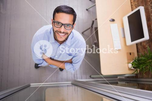 Smiling businessman with arms crossed at office