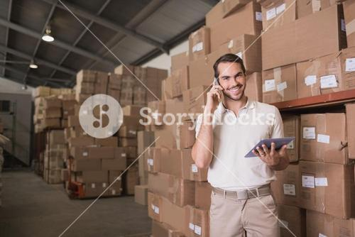 Worker with mobile phone and digital tablet in warehouse