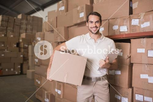 Delivery man with box and clipboard in warehouse