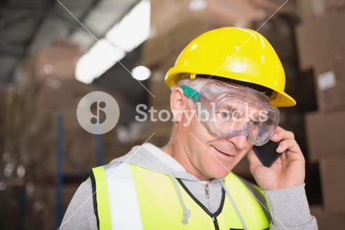 Worker using mobile phone in warehouse