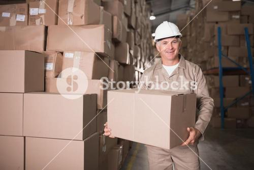 Worker carrying box in warehouse