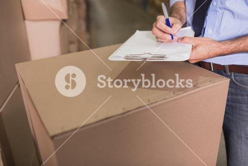 Mid section of warehouse worker with clipboard