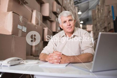 Warehouse manager with laptop at desk