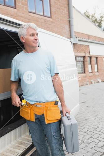 Man with tool belt and briefcase by van