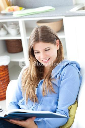 Happy woman reading a book in the living room