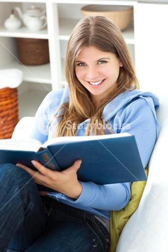 Happy woman reading a book in the living room at home