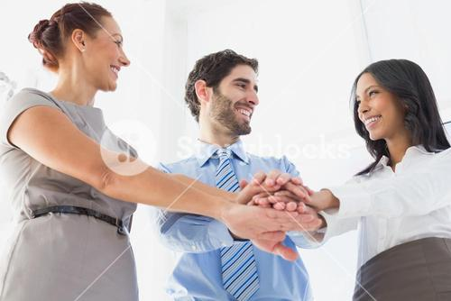 Workers with stacked hands smiling
