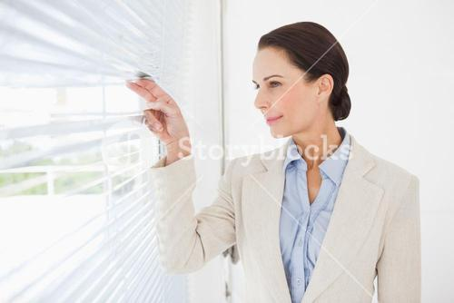 Businesswoman looking out the blinds