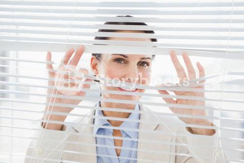 Woman glancing through some blinds