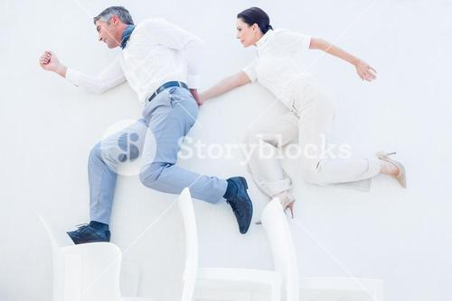 Business partners jumping over chairs