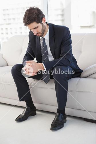 Nervous businessman sitting on couch
