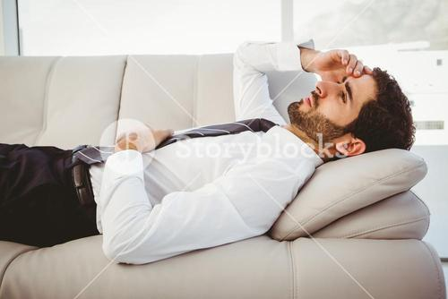 Sick businessman lying on the couch
