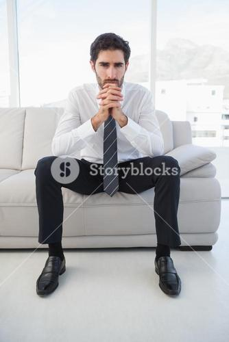Serious businessman sitting on couch