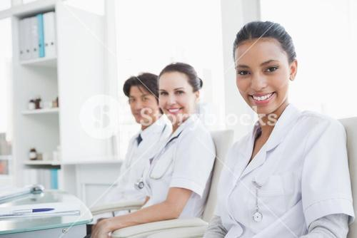Smiling doctors sitting beside each other