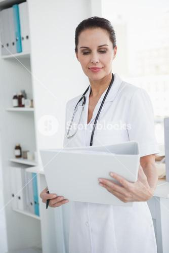 Focused doctor looking at a folder