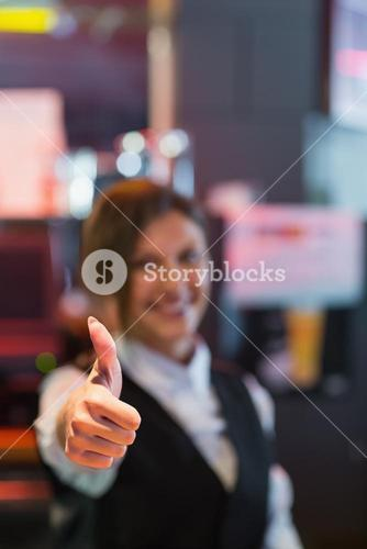 Barmaid showing thumbs up to camera