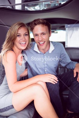 Happy couple smiling in limousine