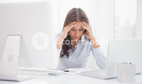 Tired businesswoman sitting at her desk