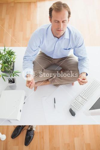 Zen businessman meditating on his desk