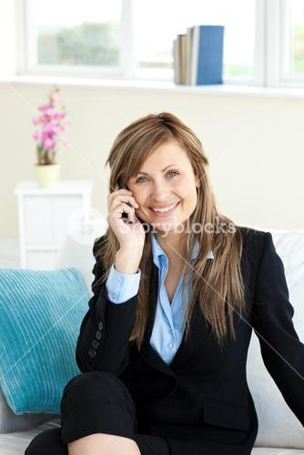 Positive businesswoman using a mobile phone i