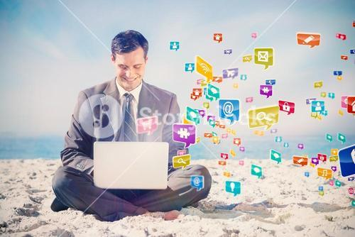 Composite image of young businessman with legs crossed typing on his laptop