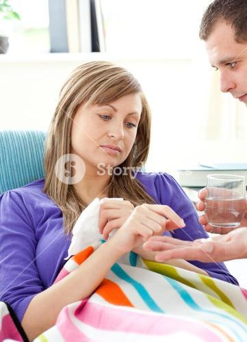 Caring boyfrieng giving his sick girlfriend pills and water