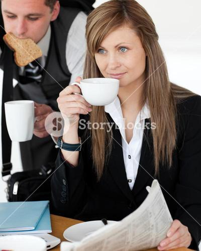 Beautiful businesswomand drinking coffee while her husband hurry up