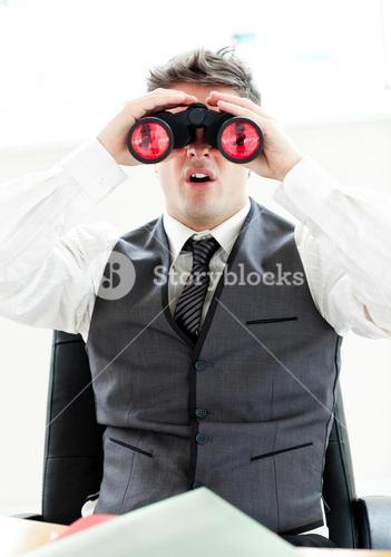 Impressed businessman looking through binoculars sitting in his office