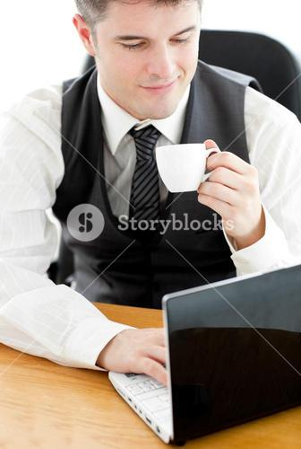 Happy young businessman looking at his laptop holding a coffee sitting at his desk