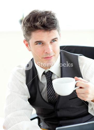 Confident young businessman with a laptop holding a coffee