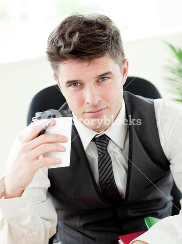 Portrait of confident businessman holing a cup od coffee in the office