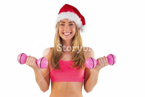 Festive fit blonde holding dumbbells