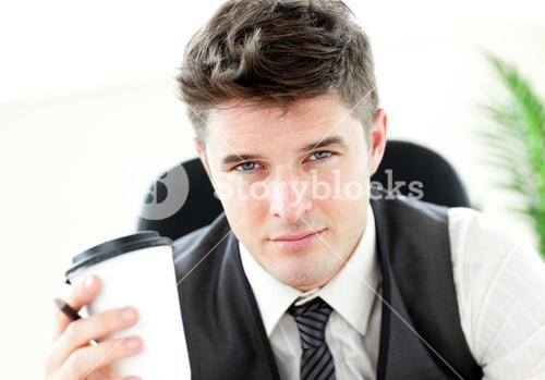 Serious businessman drinking coffee in the office