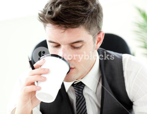 Young businessman drinking coffee in the office