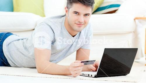 Smiling man lying on the floor with laptop holding a card