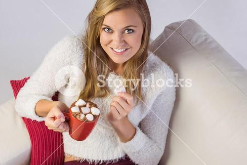 Pretty blonde enjoying hot chocolate on the couch
