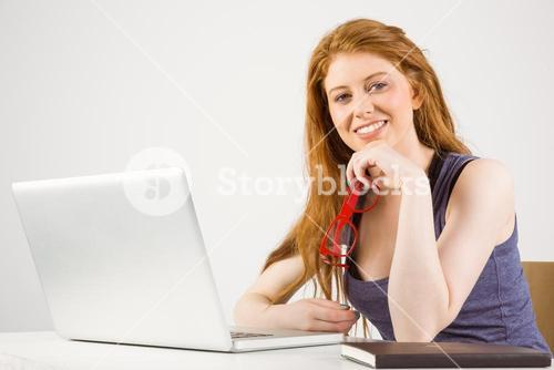 Pretty redhead working on laptop