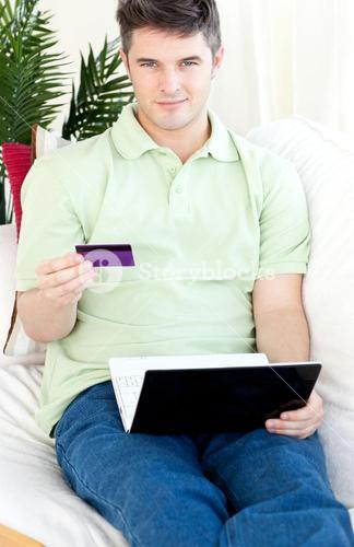 Charismatic young man with card and laptop on a sofa smiling at the camera