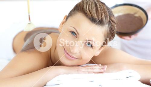 Beautiful woman enjoying a mud treatment