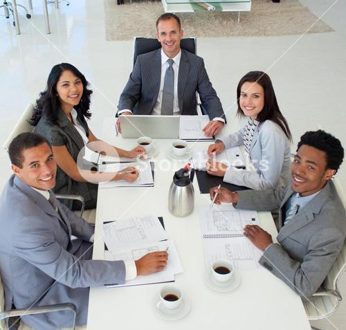 Business people in a meeting smiling at the camera
