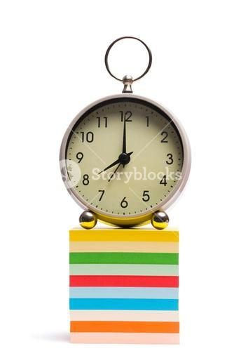 Alarm clock on pile of sticky notes