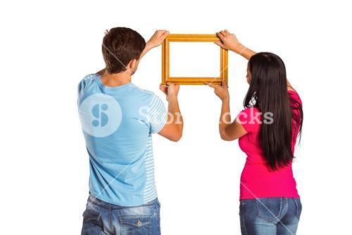 Young couple hanging a frame