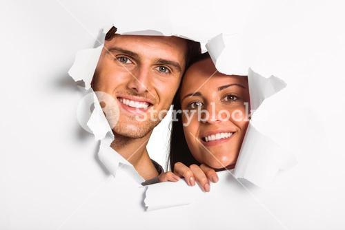 Young couple looking through paper rip