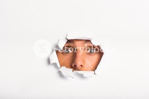 Young man looking through paper rip