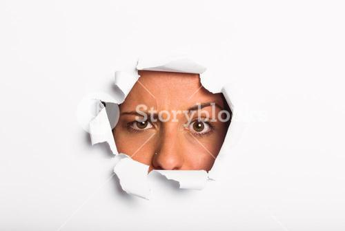 Young woman looking through paper rip