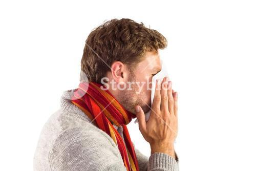 Man blowing nose on tissue