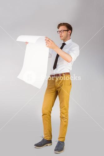 Geeky businessman reading large page