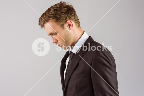 Young handsome businessman looking down
