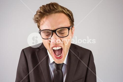 Young angry businessman shouting at camera