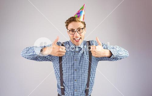 Geeky hipster wearing party hat smiling at camera